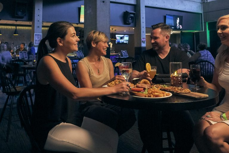 A group of friends sit at a table at Black Olive Bar & Grill sharing appetizers