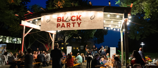 People sit at picnic tables underneath a sign for Black Olive's Block Party