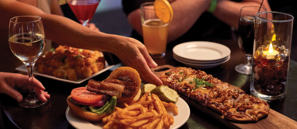 Burgers, fries, flatbreads and other appetizers sit on a table as someone reaches for a bite