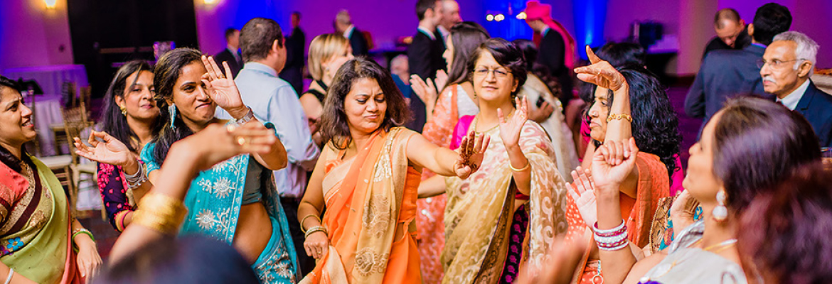 Women in colorful clothing dance at an Indian wedding reception
