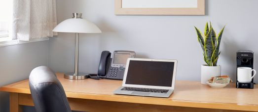 A guest room desk has a lamp, a laptop, a landline and a coffee machine