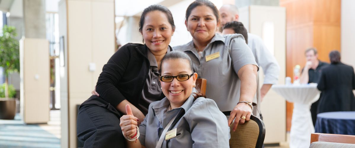 Three employees of The National Conference Center smile and pose in their uniforms