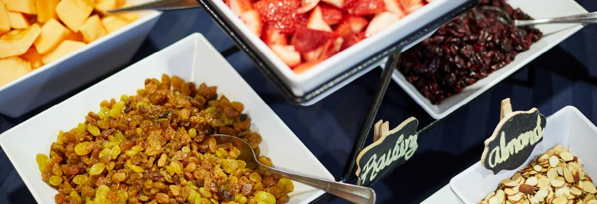 Raisons, almonds and fresh fruit are in bowls set on a table for meeting attendees' enjoyment