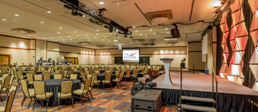 An auditorium is set up for an event with banquet-style tables, chairs and a podium on stage