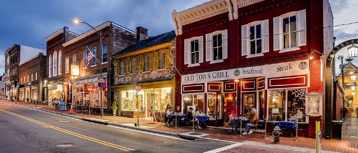 A street downtown Leesburg, Virginia at night where people dine on restaurant patios