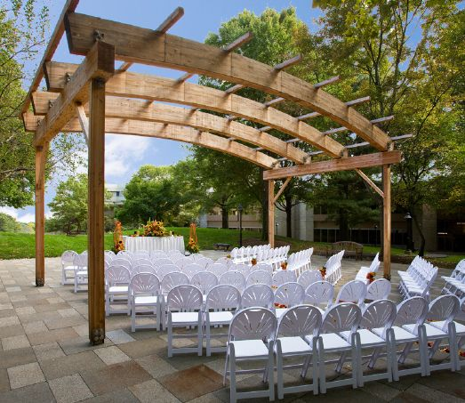 A wedding ceremony decorated in yellow and orange is set up beneath a pergola
