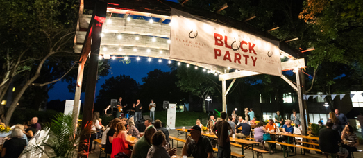 A Black Olive Block Party event taking place outside underneath the pergola