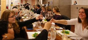 A group toasts at the table as they enjoy a Chef's Table culinary experience
