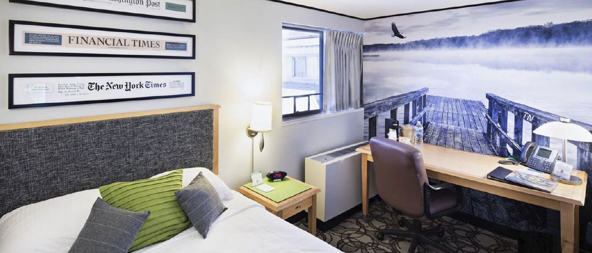 A guest room is decorated in blue and white with a wall mural of a bridge