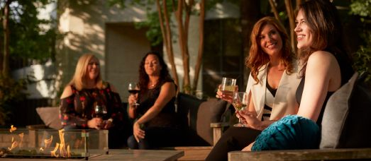 Guests at The National enjoy a glass of wine by the fire pit