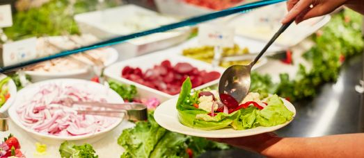 Someone builds a colorful salad at The National's salad bar in the dining room