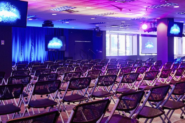 Conference hall with built-in technology (like screens and custom lighting) and chairs