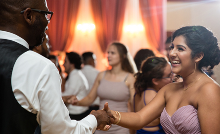 A woman in a purple dress smiles and dances with a man at a wedding