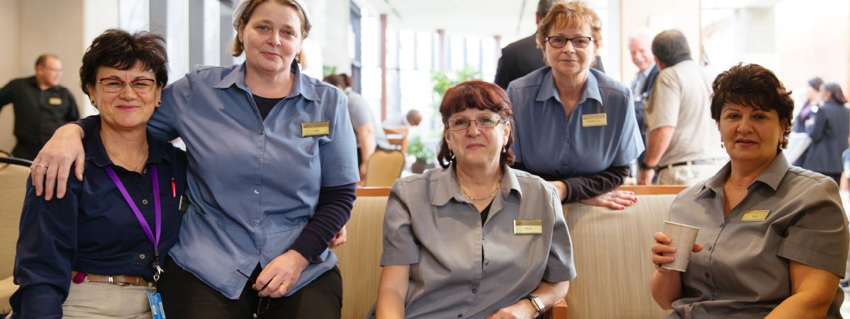 A group of five employees smile for the camera