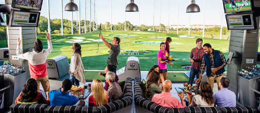 A large group of people drinking and having fun at Topgolf
