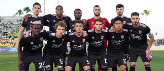 Loudoun United FC poses in uniform, which has The National's logo on it