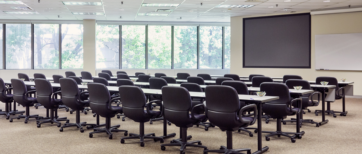 Empty meeting room with rows of tables and chairs in front of a large screen