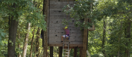 Participant climbing rock wall element of the challenge course