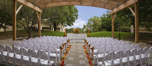 An outdoor wedding is set up with rows of white chairs beneath a pergola