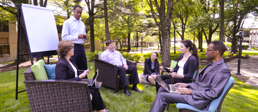 A meeting takes place outdoors with people sitting in chairs and a man writing on an easel pad.