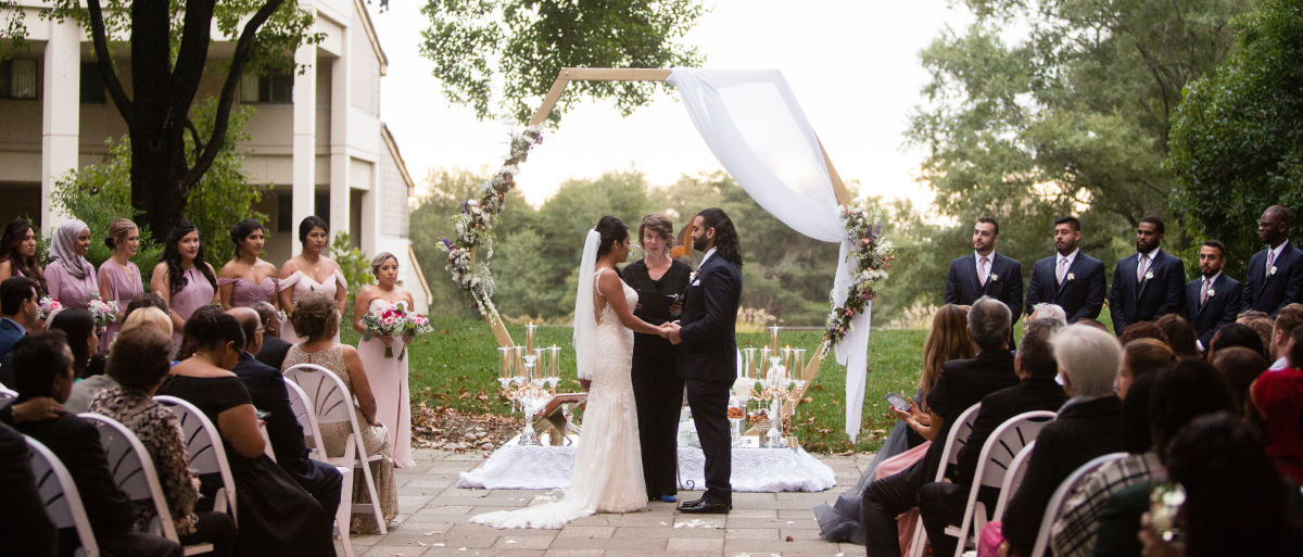 A couple stands in front of a hexagonal wedding arbor and exchanges vows at their wedding