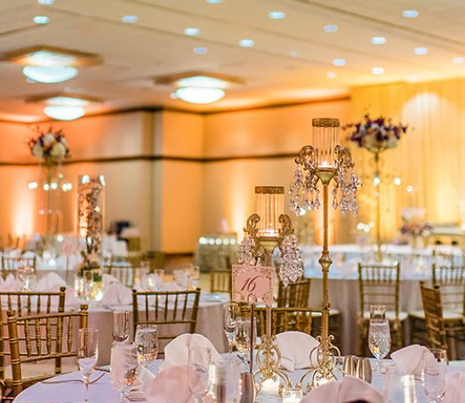 Tables are decorated for a wedding in pink, whites and gold