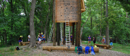 A rock climbing element on The National's challenge course is sized up by a team
