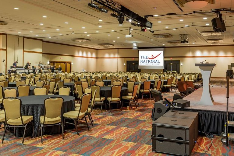 An auditorium is set up for a gala with banquet-style tables and a podium on the stage.
