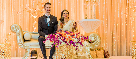 A newlywed couple sits on a gold chaise behind a large bouquet