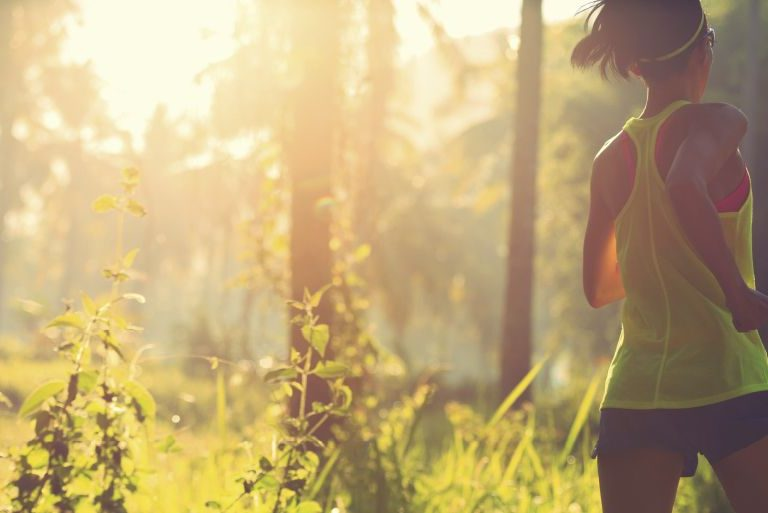 A woman in running clothes jogs along a wooded path