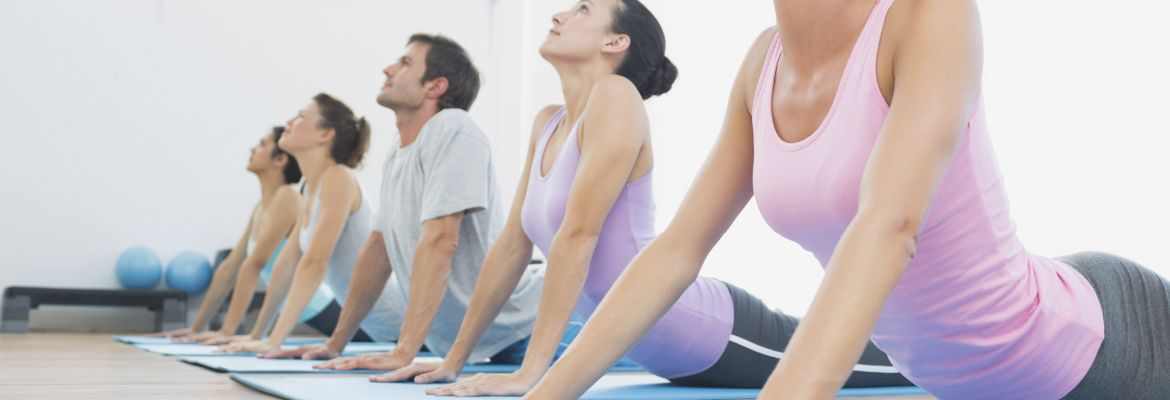 A group in the upward dog pose at a yoga class