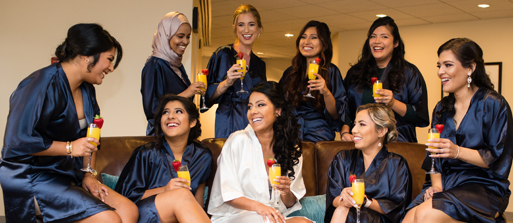 A bridal party gets ready in navy and white robes and enjoys some mimosas